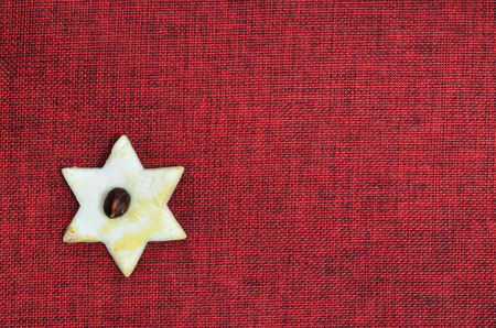 1 2 month: close up of a Christmas cookie, star shape with hazelnut, red on canvas with copy space, horizontal