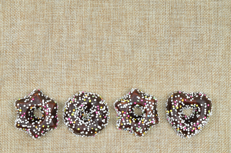 hundreds and thousands: close up of four Christmas cookies with chocolate and hundreds and thousands, star shaped and heart shaped, on canvas with copy space, horizontal