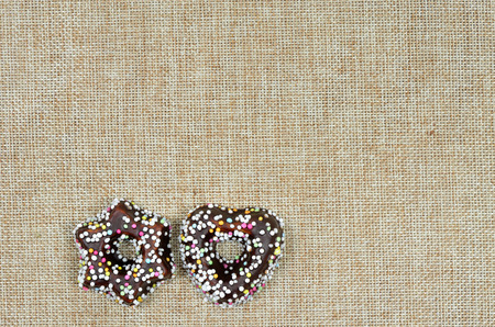 hundreds: close up of two Christmas cookies with chocolate and hundreds and thousands, star shaped and heart shaped, on canvas with copy space, horizontal