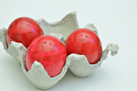 veined: red Easter eggs in a cardboard box, close up, isolated on white background, horizontal