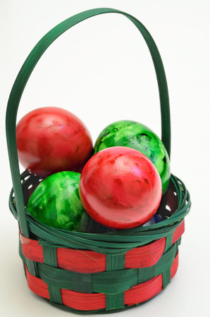 marmorate: red and green Easter eggs in a basket, close up, isolated on white background, vertical Stock Photo