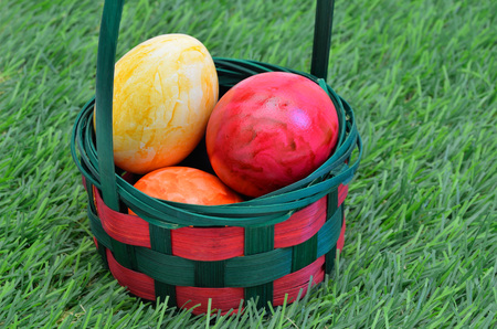 marmorate: colorful Easter eggs in a basket, outside on green grass, close up Stock Photo