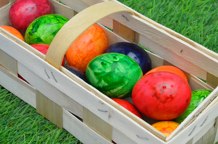 grass close up: colorful Easter eggs in a basket, outdoors on green grass, close up, slanted, full frame, horizontal