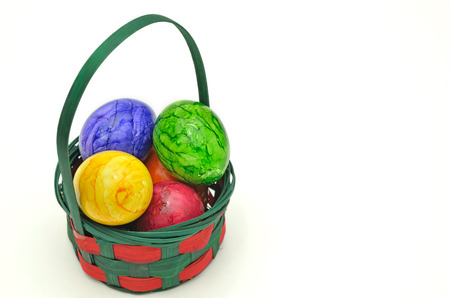 marmorate: colorful Easter eggs in a basket, close up, isolated on white background, vertical Stock Photo