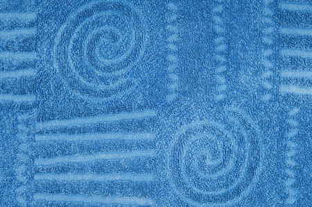 toweling: close up of a cyan, blue terry towel with geometrical and spiral pattern, horizontal Stock Photo