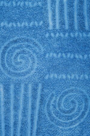 toweling: close up of a cyan, blue terry towel with geometrical and spiral pattern, vertical Stock Photo