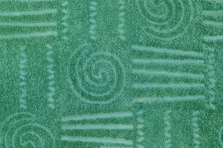 toweling: close up of a green terry towel with geometrical and spiral pattern, horizontal