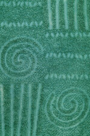 toweling: Close up of a green terry towel with geometrical pattern and spiral, vertical