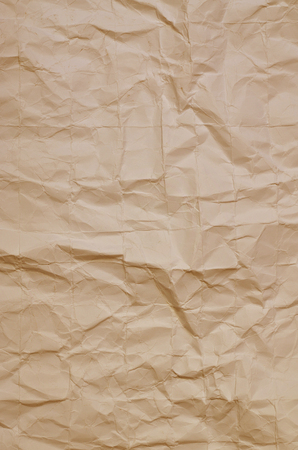 full of holes: Close up of a creased, ocher paper texture, full frame, vertical Stock Photo