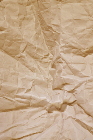 creasy: Close up of a creased, ocher paper texture, full frame, vertical Stock Photo