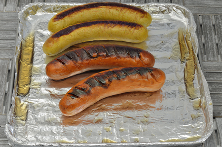 brazier: Four grilled sausages on grill with silver foil, close up, macro, full frame