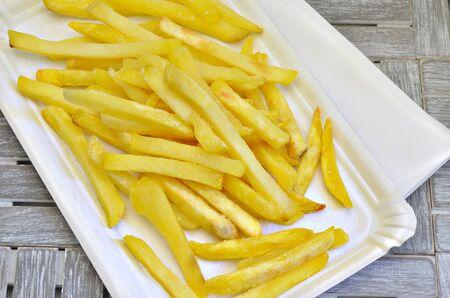 Pommes frites on white paper plate, close up, macro, full frame, gray background Stock Photo