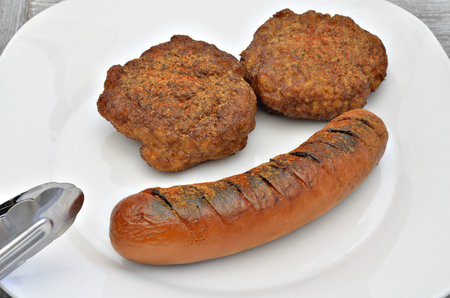 Two meatballs and a grilled sausage on white plate, close up, macro, full frame, gray background Zdjęcie Seryjne
