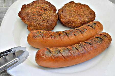 Two grilled sausages and two meatballs on white plate, close up, macro, full frame, gray background