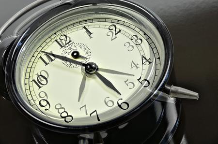 Close up of two, overlapping images with retro alarm clocks, showing different times, horizontal, slanted
