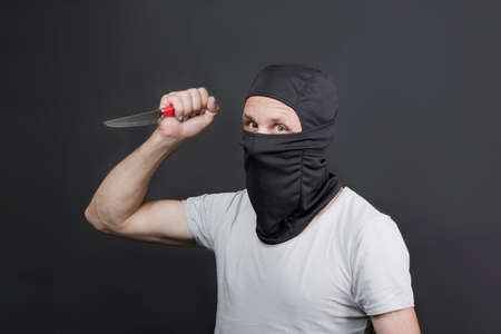 Metal knife in the hand of caucasian man in black mask. The criminal with a knife weapon threatens to kill. With space for an inscription. News staties, newspaper, social issues. american man
