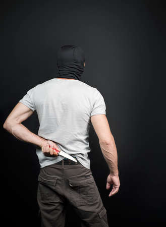 An evil, bandit criminal, american man holds a kitchen knife as weapon behind his back, waiting for the victim. A maniac, thief, gangster and a rapist with a knife in black mask. Back view, Copy space