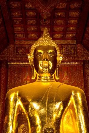 gold buddha statue in Wat Phra That Lampang Luang photo