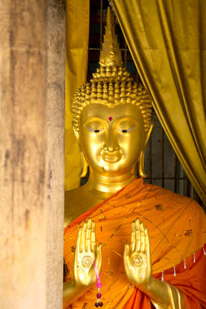 gold buddha statue and wood  pole in Wat Phra That Lampang Luang photo