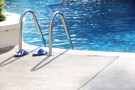 swim shoes: blue sandal near the swimming pool ladder Stock Photo