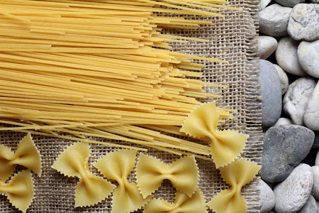 fray: spaghetti farfalle on Burlap fray and the river rock Stock Photo