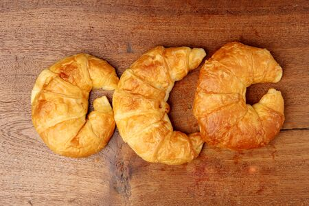 teakwood: croissant bakery on teakwood table lighting and gray background top view