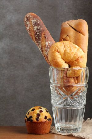 teakwood: croissant brad muffin bakery in glass blow on teakwood table lighting and gray background