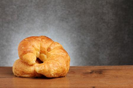 teakwood: croissant bakery on teakwood table lighting and gray background