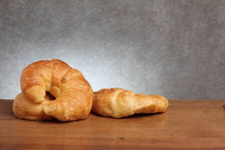 gold teakwood: croissant bakery on teakwood table lighting and gray background
