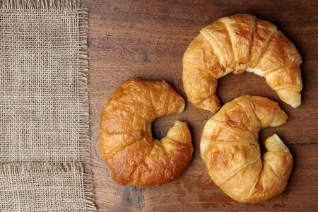 buttery: croissant bakery on teakwood table lighting and gray background top view
