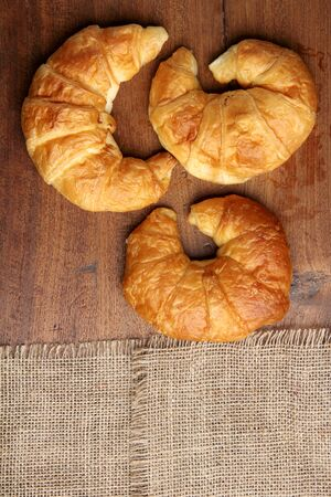 gold teakwood: croissant bakery on teakwood table lighting and gray background top view