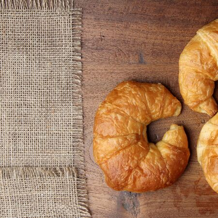 gold teakwood: croissant bakery on teakwood table lighting and gray background top view square format Stock Photo