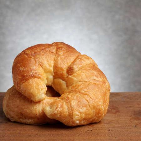 teakwood: croissant bakery on teakwood table lighting and gray background square format Stock Photo
