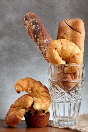 teakwood: croissant brad muffin baguette bakery in glass blow on teakwood table lighting and white background burlap