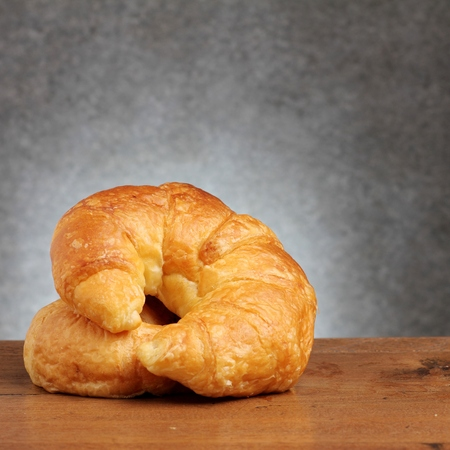 teakwood: croissant bakery on teakwood table lighting and gray background square format Stock Photo