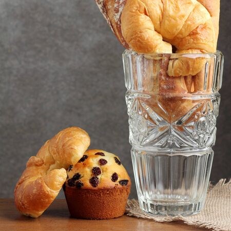 croissant brad muffin  bakery in glass blow on teakwood table lighting and gray background square format Stock Photo