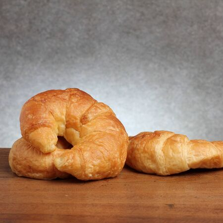 gold teakwood: croissant bakery on teakwood table lighting and gray background square format Stock Photo