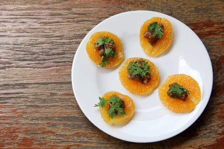 Thai appetiser Ma Haw. snack cuisine food on orange slice on wood table texture. Lots of copy space Imagens