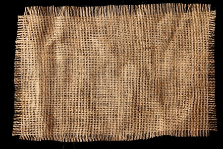 hessian: Burlap hessian with frayed edges on black background Stock Photo