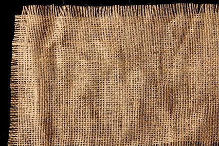 frayed: Burlap hessian with frayed edges on black background Stock Photo