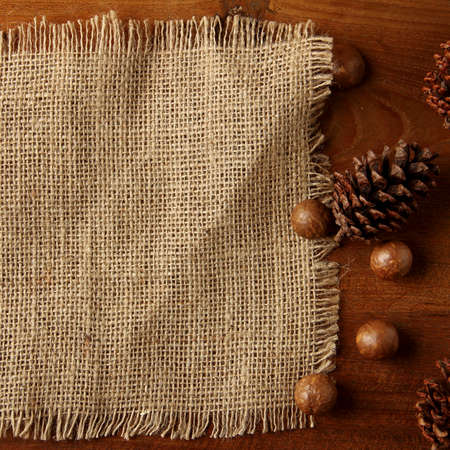 teakwood: burlap on teakwood board  with cones araucaria almond nut with lot of copy space square format Stock Photo