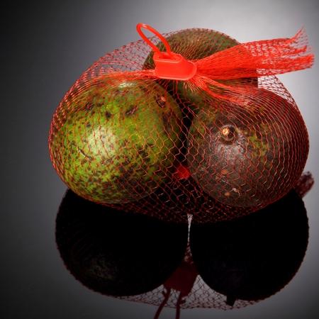 high light: fresh avocado fruit in plastic net sack studio shot high light background square format