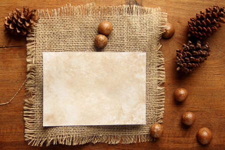 teakwood: paper burlap on teakwood board  with cones araucaria almond nut with lot of copy space