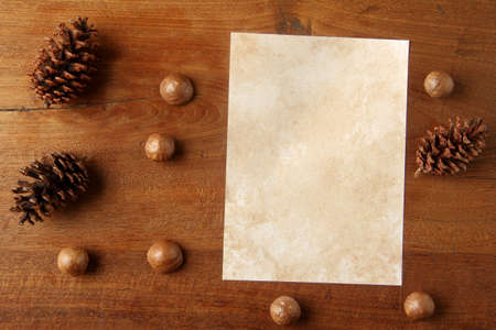 teakwood: paper on teakwood board with cones araucaria almond nut with lot of copy space