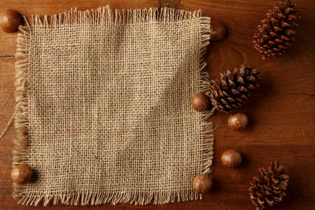 teakwood: burlap on teakwood board  with cones araucaria almond nut with lot of copy space Stock Photo