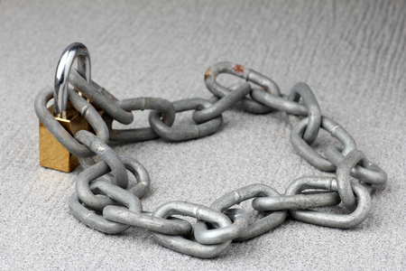 key to freedom: iron chain lock key on rock texture background Stock Photo