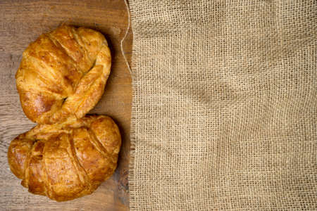 gold teakwood: croissant bakery on burlap teak wood table lighting and gray background top view Stock Photo