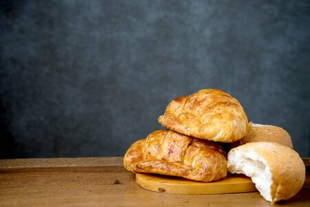 gold teakwood: croissant bakery and half bun on teak wood table lighting and gray background