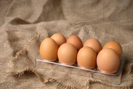 frayed: egg on burlap material background hessian with frayed edges plastic tray