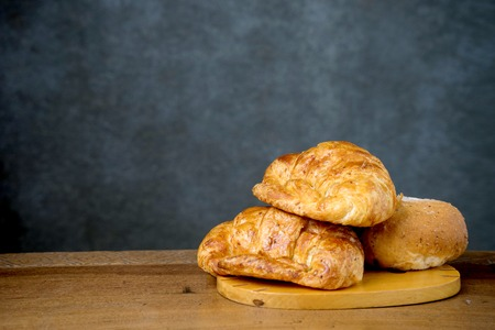 gold teakwood: croissant bakery on teak wood table lighting and gray background